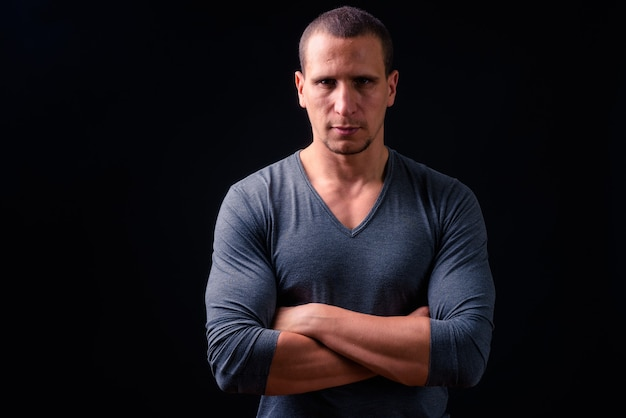 Muscular persian man with short hair looking macho against black wall