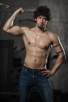 Muscular person trains in gym, performs exercise on hands, bare torso, muscles are strained
