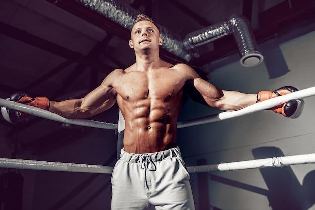 次の試合のトレーニング中にリングの隅にあるロープで休む筋肉のプロキックボクサー