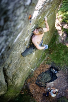 Muscular rock climber climbs on cliff wall with rope