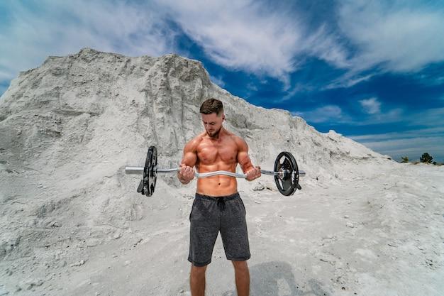 屋外でバーベルでエクササイズをしている筋肉のセクシーな男。ボディービルとアウトドアスポーツのコンセプト。採石場での写真撮影。
