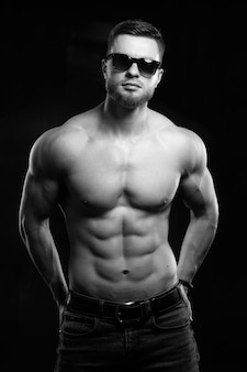 Muscular and sexy man. naked torso of young man with perfect abs. black and white. half turned to the camera. closeup.
