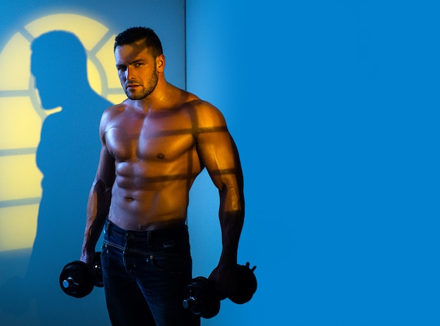 Muscular sexy man with naked torso is posing with dumbbell.
