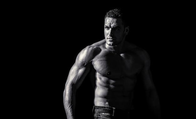 Мускулистый сексуальный мужчина с торсом. мускулистая модель спортивный молодой человек на темном фоне. чувственный мужчина с обнаженным сильным животом. мускулистый торс крупным планом. концепция торса. модный портрет сильного брутального парня
