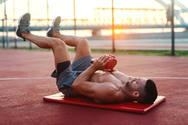 Muscular shirtless caucasian man with serious facial expression doing exercises with kettlebell while lying on the mat on court in the morning.