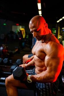 Мускулистый мужчина без рубашки делает упражнения на бицепс с упражнениями с гантелями в рамках своей тренировки по бодибилдингу. фитнес-мотивация, спортивный образ жизни, здоровье, спортивное тело