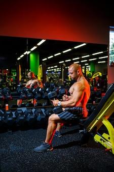 彼のボディービルのトレーニングの一部としてダンベルのエクササイズで上腕二頭筋のエクササイズをしている筋肉の上半身裸の男。フィットネスモチベーション、スポーツライフスタイル、健康、運動体