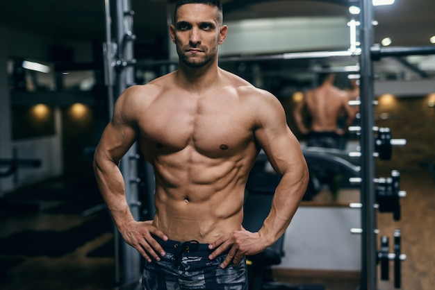 Muscular shirtless man with hands on hips posing in a gym