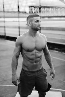 深刻な表情でポーズをとって、朝のコートに立っている間よそ見筋肉の上半身裸の男。黒と白の写真。