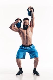 Мускулистая татуированная бородатая тренировка культуриста спортсмена без рубашки с гирей на белой стене. изолировать