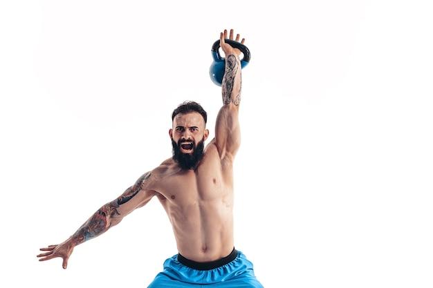 Мускулистый татуированный бородатый мужчина без рубашки культурист тренируется с гирями