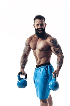Muscular shirtless tattooed bearded male athlete bodybuilder workout with kettlebell
