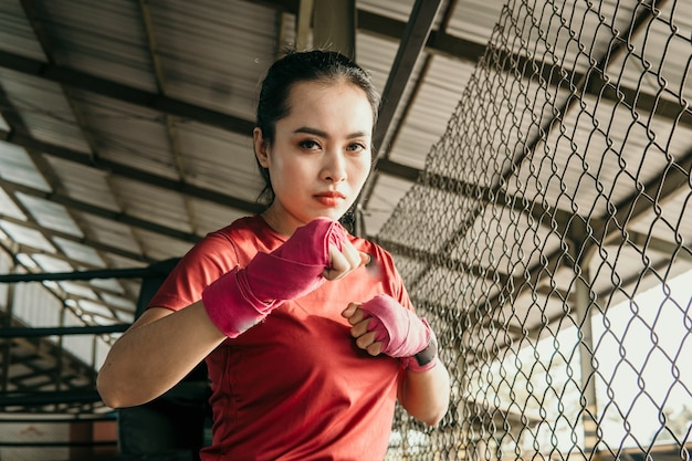 Muscular sports girl boxing workout over fighting place