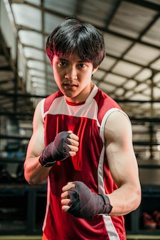 Muscular sports guy boxing workout over fighting place
