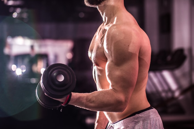 Muscular sports man is engaged in training cross fit in the gym ,the concept of sport