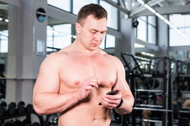 Muscular sports man use activity tracker