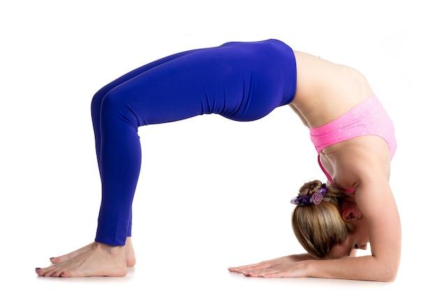 Muscular sportswoman doing bridge pose
