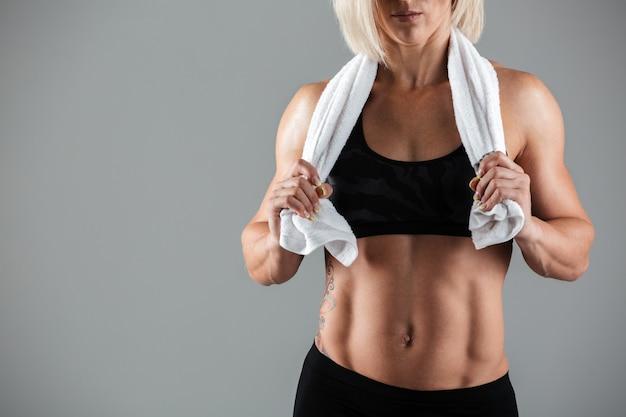 Мускулистая спортсменка держит полотенце