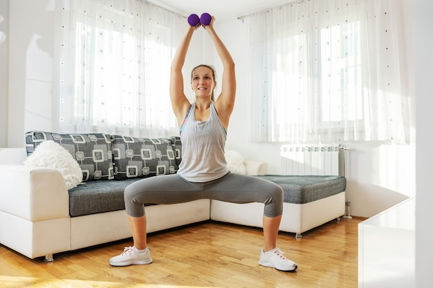 Muscular sportswoman in shape standing with split legs and lifting dumbbells.
