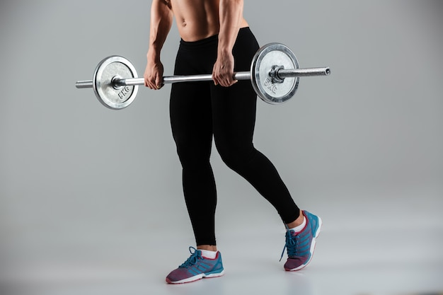 Muscular sportswoman standing with a barbell