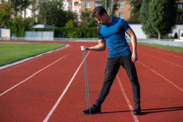 スタジアムで屋外の弾性輪ゴムでトレーニングをしている筋肉のスポーティな男。テキスト用のスペース