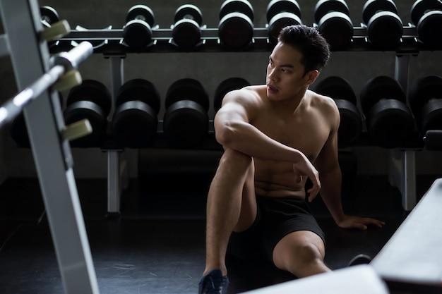 누드 몸통을 가진 근육질의 강한 아시아 청년은 피트니스 체육관의 랙 근처에서 아령 이두박근 운동을 한 후 휴식을 취합니다. 보디 빌딩 및 건강한 스포츠 라이프 스타일 개념입니다.