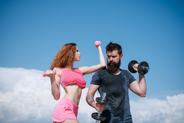 Muscular and strong. sexy woman and hipster having muscular build and physical fitness. muscular couple doing muscle training with dumbbells. fit girl and strong bearded man developing muscular power.