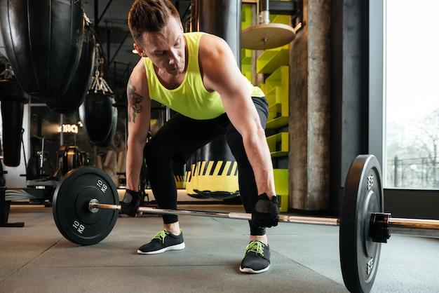 Мускулистый сильный спортсмен поднимая штангу