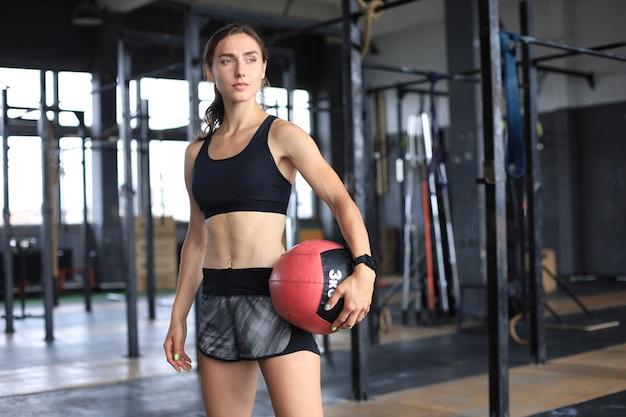 クロスフィットジムで薬のボールを運ぶ筋肉の強い女性。