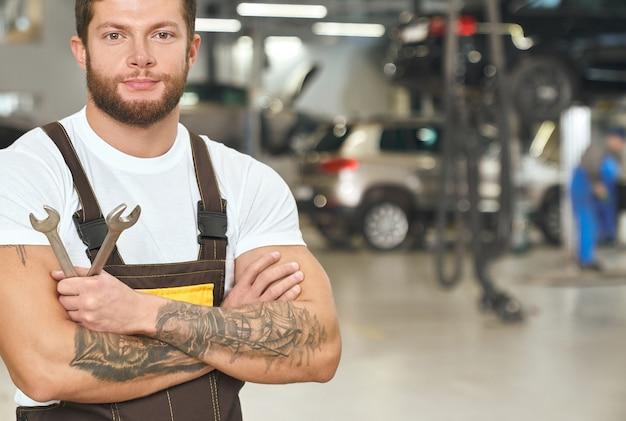 Мускулистый, татуированный ремонтник позирует в автосервисе.