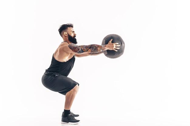 白い壁に隔離されたスタジオでフィットネスウェイトメディスンボールを行使する筋肉の入れ墨ひげを生やした男性。