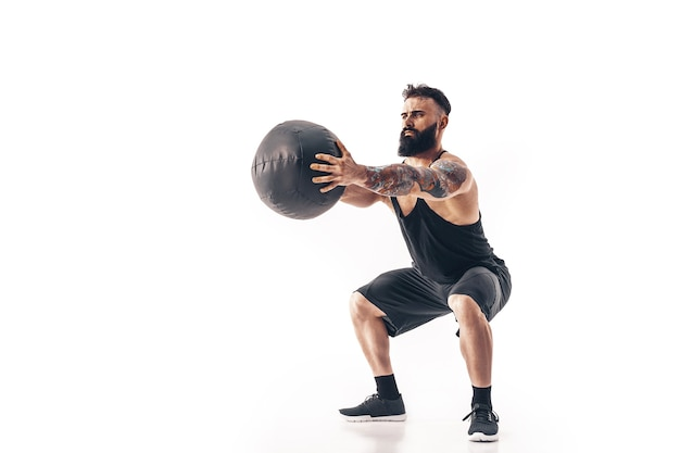 Мускулистый татуированный бородатый мужчина, выполняющий фитнес-весы, медицинский мяч, изолированный на белой стене.