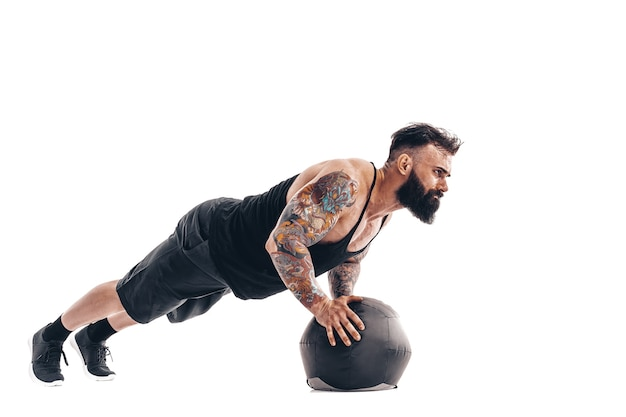 Мускулистые татуированные бородатые мужчины, тренирующиеся с весами для фитнеса, отжимания с мячом