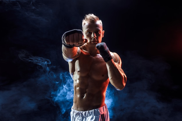Muscular topless fighter in boxing gloves