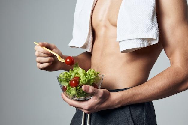 筋肉質のトルソマンサラダプレート健康的な食事ライフスタイルトリミングビュー
