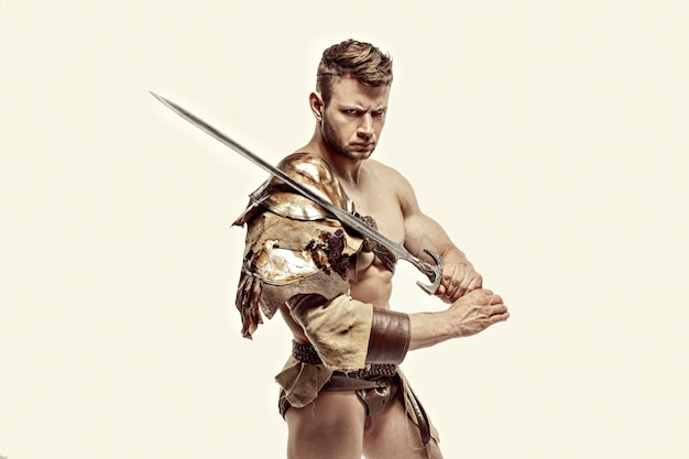 Muscular warrior with sword against of white background