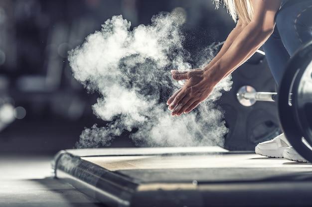 ダンベルでジムでバーベルトレーニングの前に手をたたく筋肉重量挙げの女性。