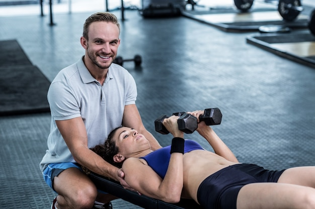 A muscular woman about to lift dumbbells