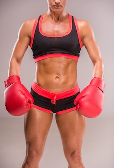 Muscular woman in boxing gloves
