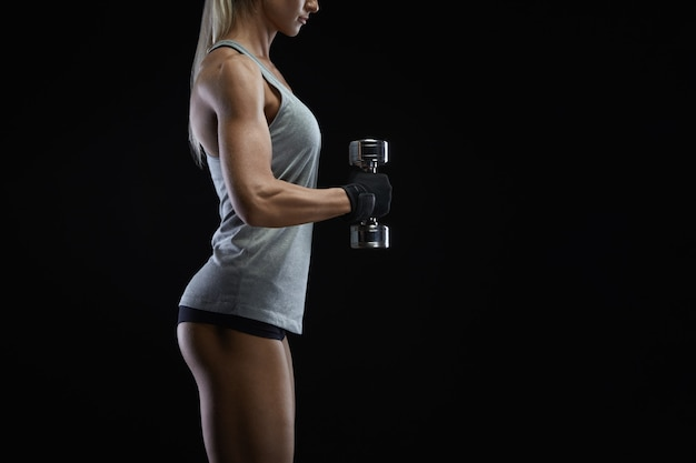 Muscular woman curling dumbbells