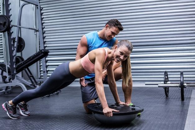 Muscular woman doing bosu ball exercises