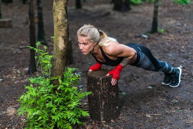 公園のストリートトレーニングで腕立て伏せを行う筋肉の女性