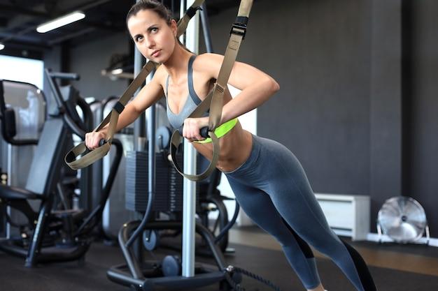 ジムで腕立て伏せトレーニングアームをtrxフィットネスストラップでやっている筋肉質の女性。