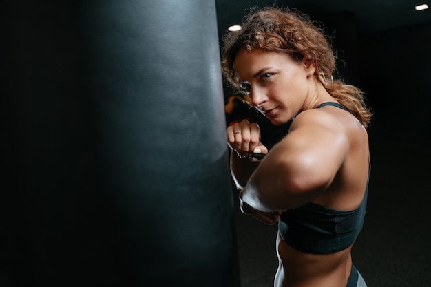 Muscular woman in a fighting pose on a black background hitting a boxing bag concept of fitness and ...