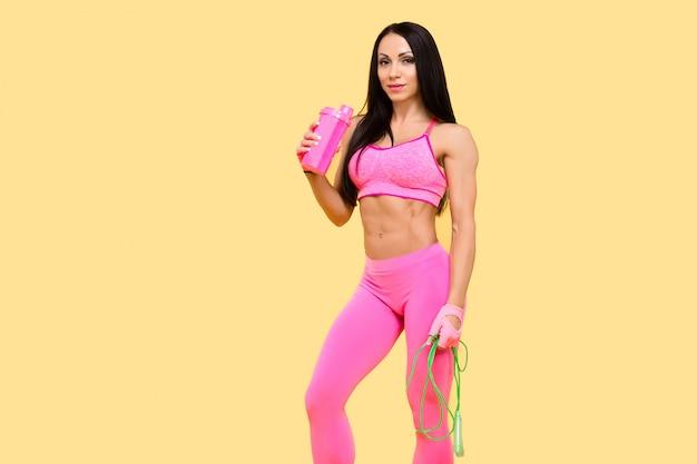 Muscular woman in fitnesswear drinking from the bottle