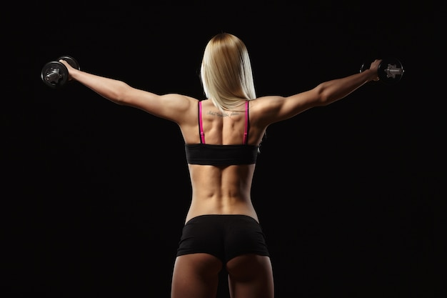 Muscular woman on his back lifting weights on a black background