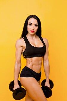 Muscular woman holding dumbbells