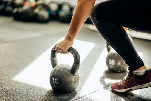 Muscular woman holding old and rusty kettle bell on to the gym floor
