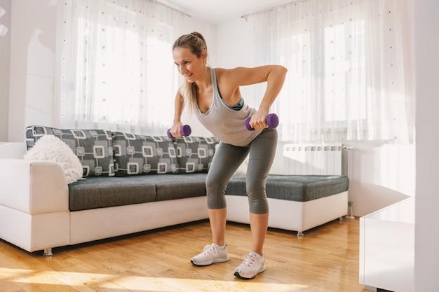 体調の良い筋肉質の女性が前屈みになり、ダンベルを使ってフィットネスを練習します。彼女は背中の運動をしています。