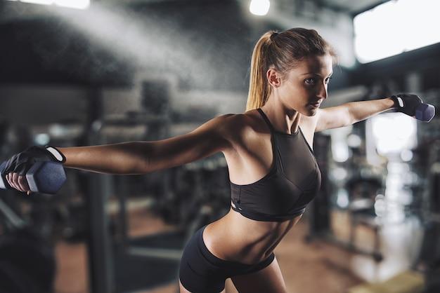 筋肉質の女性がジムでトレーニングしています